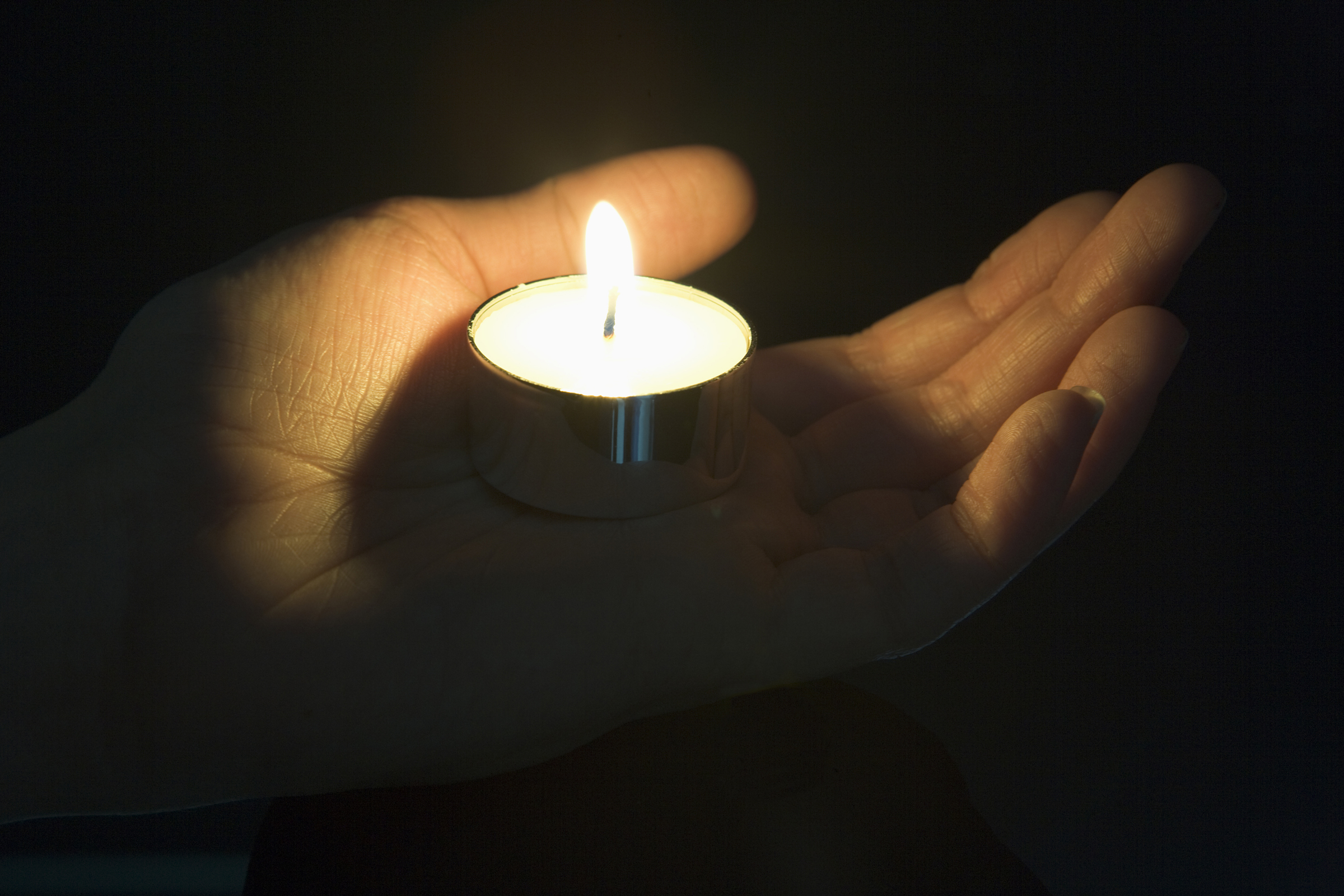 Close-Up Of Candle In The Palm Of A Persons Hand